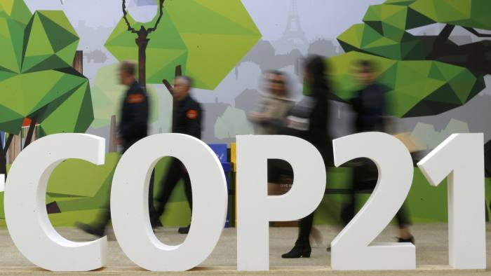 People walk walks past the COP21 logo in the Climate Generations area during the World Climate Change Conference 2015 (COP21) at Le Bourget, near Paris, France, December 1, 2015. REUTERS/Stephane Mahe