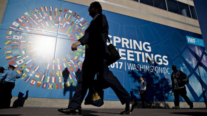 Pedestrians walk past an International Monetary Fund (IMF) and World Bank spring meeting sign in Washington, D.C., U.S., on Tuesday, April 18, 2017. The emergence of protectionist forces could undermine a modest brightening of the global growth outlook and is putting severe strain on the post-World War II economic order, the IMF said today. Photographer: Andrew Harrer/Bloomberg
