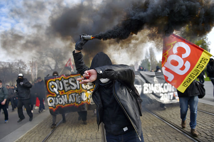 TOPSHOT - A protestor holds a flare during a nationwide protest day against the government's economic and social reforms, on November 16, 2017 in Nantes. / AFP PHOTO / LOIC VENANCELOIC VENANCE/AFP/Getty Images