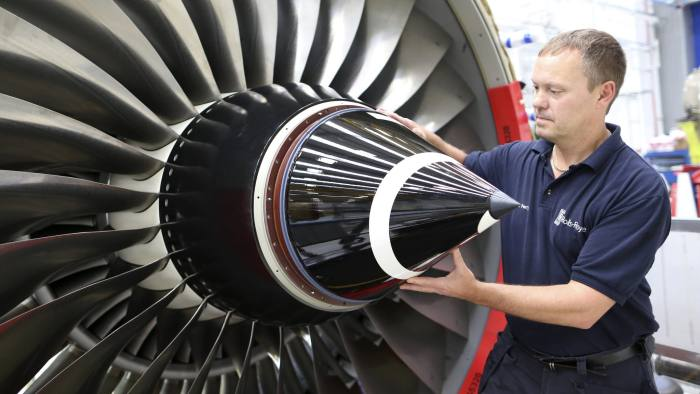 An employee fits the nose cone to a Trent 700 aircraft engine on the production line at the Rolls-Royce Holdings Plc factory in Derby, U.K., on Wednesday, Aug. 19, 2015. Rolls-Royce's XWB engine developed for the Airbus A350 should bring in twice the cash flow than the existing Trent 700 model on the Airbus A330, Chief Executive Warren East said in July. Photographer: Chris Ratcliffe/Bloomberg