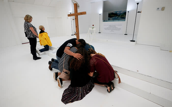 People pray in the First Baptist Church of Sutherland Springs where 26 people were killed in a shooting attack last week, as the church was opened to the public as a memorial to those killed, in Sutherland Springs, Texas, U.S.