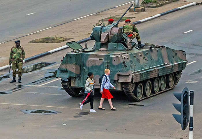 "TOPSHOT - Young women walk past an armoured personnel carrier that stations by an intersection as Zimbabwean soldiers regulate traffic in Harare on November 15, 2017. Zimbabwe's military appeared to be in control of the country on November 15 as generals denied staging a coup but used state television to vow to target ""criminals"" close to President Mugabe. / AFP PHOTO / Jekesai NJIKIZANAJEKESAI NJIKIZANA/AFP/Getty Images"
