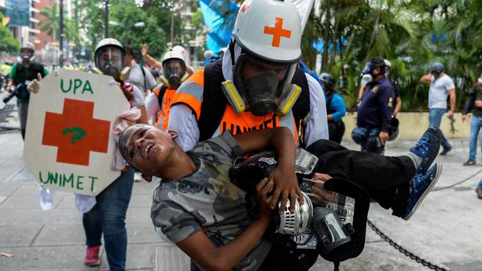 TOPSHOT - Medical staff carry a boy suffering from the effects of tear gas during clashes between opposition demonstrators and the riot police during a protest against President Nicolas Maduro's government in Caracas, on May 30, 2017. Two leading Venezuelan opposition figures were wounded in anti-government protests Monday, as demonstrators vowed to intensify pressure on Maduro and against his plans to hold a constitutional assembly. / AFP PHOTO / Federico PARRAFEDERICO PARRA/AFP/Getty Images