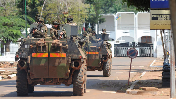 French soldiers in an armored vehicle patrol in front of the presidential palace in Bangui