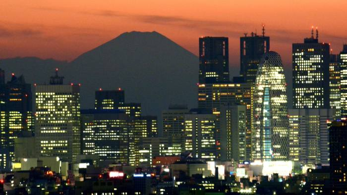 Japan's highest mountain Mount Fuji (top C) is seen behind the skyline of the Shinjuku area of Tokyo at sunset on November 27, 2014. Tokyo stocks lost 0.78 percent on November 27 as a stronger yen took the wind out of the market ahead of the US Thanksgiving holiday. AFP PHOTO / KAZUHIRO NOGIKAZUHIRO NOGI/AFP/Getty Images