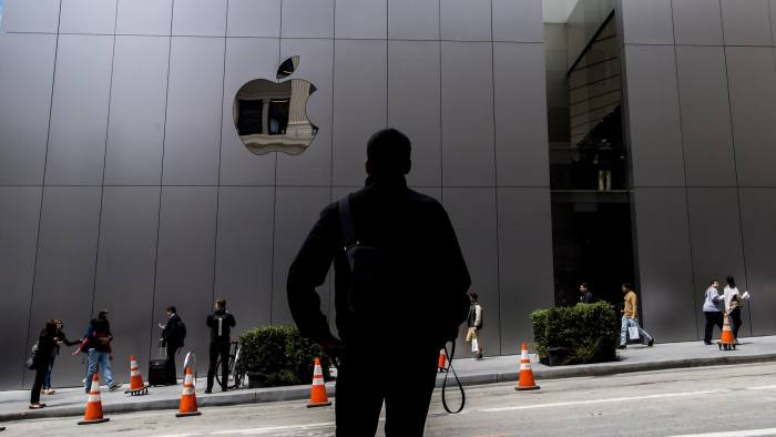 """A pedestrian stands across the street from the new Apple Inc. flagship store at Union Square during the grand opening in San Francisco, California, U.S., on Saturday, May 21, 2016. The flagship location boasts 40-foot-tall doors opening onto the square and comprises five departments, or what Apple prefers to call """"features."""" Photographer: David Paul Morris/Bloomberg"""