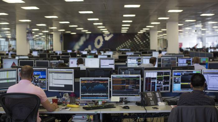 Dealers look at financial data on computer screens on the trading floor of IG Group Holdings Plc in London