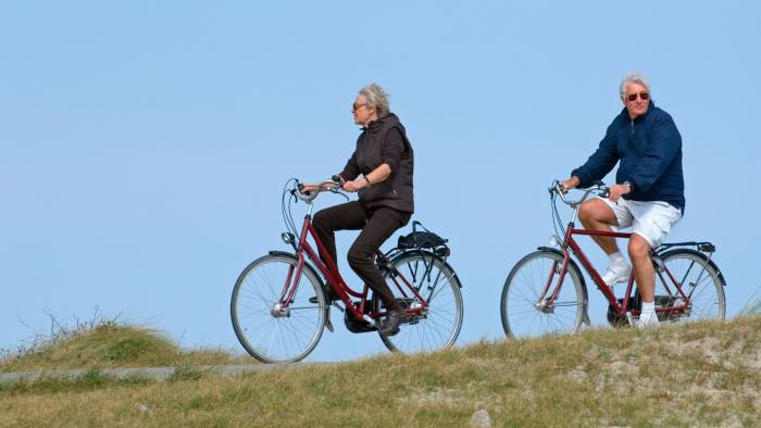 BEMBNW Elderly cyclists on bicycles riding in the dunes along the North Sea coast