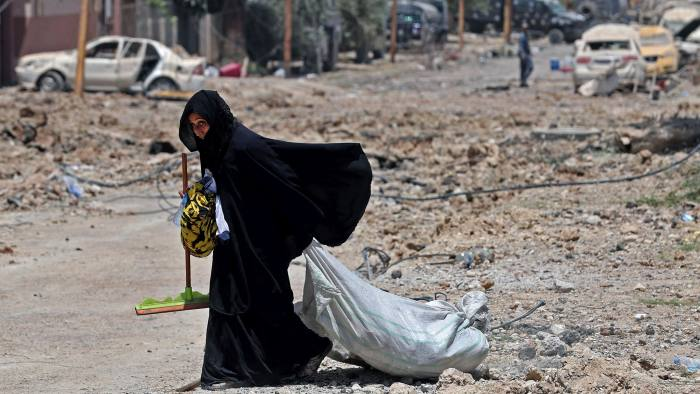 TOPSHOT - A displaced Iraqi woman carries her belongings as she evacuates her home in western Mosul's Zanjili neighbourhood as government forces advance in the area during their ongoing battle against Islamic State (IS) group fighters on May 31, 2017. / AFP PHOTO / KARIM SAHIBKARIM SAHIB/AFP/Getty Images