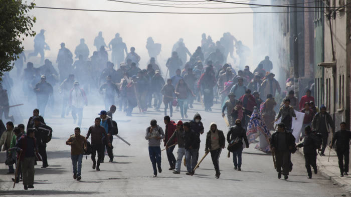 Farmers run away from tear gas fired by riot police during a protest by coca leaf farmers, in La Paz, Bolivia, Tuesday, Feb. 21, 2017. The farmers from a region north of La Paz known as Los Yungas, were dispersed by police with tear gas bombs during a protesting march, after a three-day vigil near the government palace and the National Congress where they had gathered to protest a bill they believe favors coca leaf farmers represented by President Evo Morales. (AP Photo/Juan Karita)