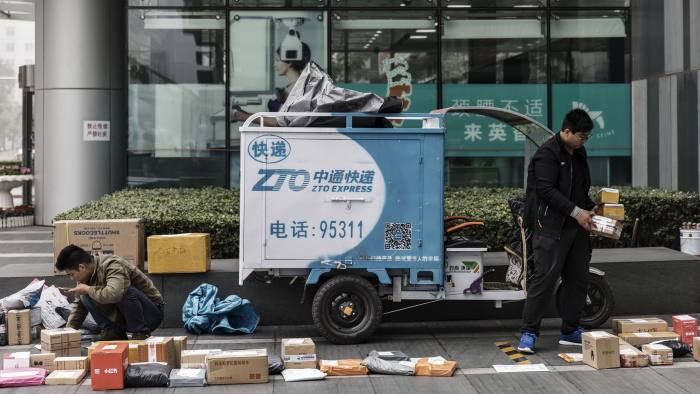 People sort through packages next to a ZTO Express Co. delivery vehicle outside an office building in Beijing, China, on Wednesday, Oct. 19, 2016. This year's full meeting of the party's Central Committee, or plenum, could prove pivotal in President Xi Jinping's four-year effort to consolidate power. Photographer: Qilai Shen/Bloomberg