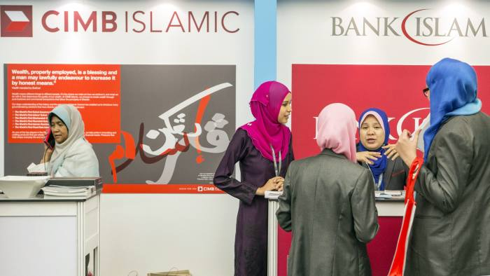 Women stand at the CIMB Islamic Banking Bhd. and the Bank Islam Malaysia Bhd. booths at the Global Islamic Finance Forum in Kuala Lumpur, Malaysia, on Wednesday, Sept. 3, 2014. The forum runs through Sept. 4. Photographer: Charles Pertwee/Bloomberg