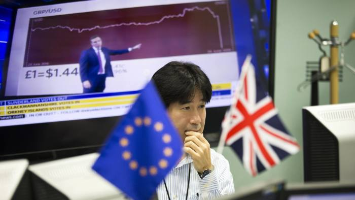 "An employee works in front of computer monitors near a European Union (EU) flag, left, and a British Union Flag, also known as a Union Jack, at a foreign exchange brokerage in Tokyo, Japan, on Friday, June 24, 2016. The pound tumbled with the euro and U.K. equity index futures after early results from Britain's referendum on membership of the European Union put the ""Leave"" campaign ahead, suggesting the risk of a so-called Brexit is greater than opinion polls implied. Photographer: Tomohiro Ohsumi/Bloomberg"