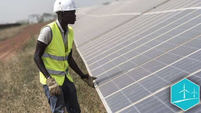 A worker inspects photovoltaic solar panels in an array at the Senergy Santhiou Mekhe PV solar plant in Thies, Senegal, on Monday, Oct. 16, 2017. The electricity produced at the 30 megawatt site, West Africa's largest to date, will be bought by the Senegal National Electricity Company (SENELEC) and injected into the national network. Photographer: Xaume Olleros/Bloomberg