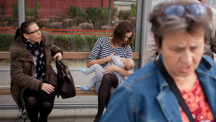 While you wait: Marta Andreasik breastfeeds her six-month-old daughter Amelia at a bus stop in Warsaw