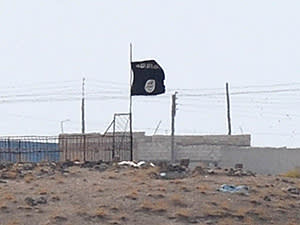 An Isis black flag near the Syrian town of Kobani, photographed in October from the Turkish-Syrian border