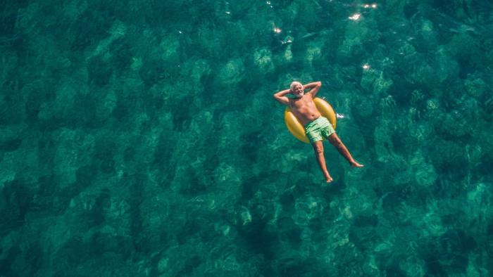 High angle view photo of a senior man relaxing while floating in the ocean using swimming tube; wide photo dimensions