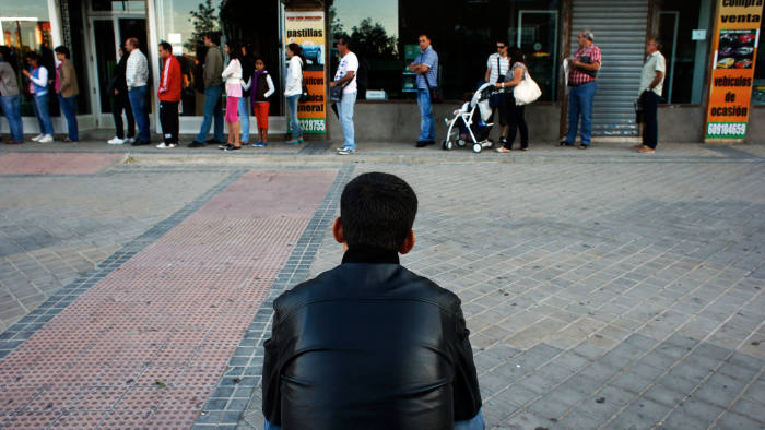 People wait to enter a government-run employment office in Madrid September 4, 2012