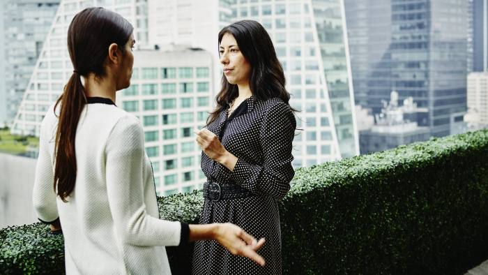 Female business executives standing in discussion on office terrace overlooking city