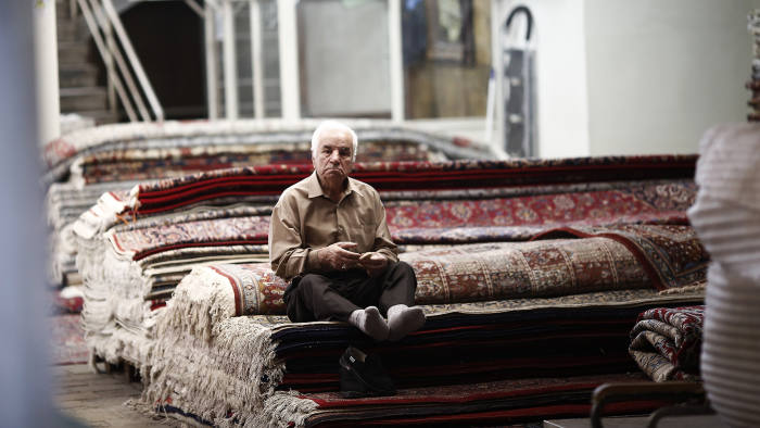 """A carpet trader sits with his shoes off as he waits for customers for Persian rugs in the Grand Bazar in Tehran, Iran, on Saturday, Aug. 22, 2015. Iran plans to raise oil production """"at any cost"""" to defend the country's market share and backs calls for an emergency OPEC meeting to help shore up crude prices. Photographer: Simon Dawson/Bloomberg"""