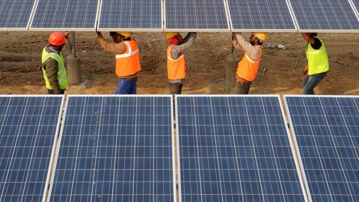 Indian workers construct part of the France-India Solar Direct Punjab Solar Park project in Muradwala