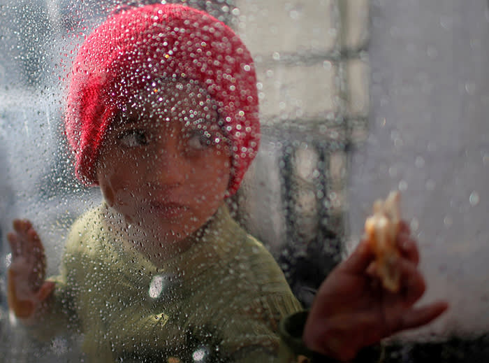 A Palestinian girl looks through a plastic sheet as raindrops are seen, outside her family's house in Al-Shati refugee camp in Gaza City January 17, 2018. REUTERS/Mohammed Salem     TPX IMAGES OF THE DAY