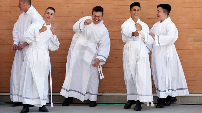 Altar boys wait to see Pope Francis outside the church of the Parish of San Pier Damiani at Casal Bernocchi on the southern outskirts of Rome, Italy