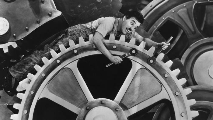 ca. 1936 --- Silent film comedian Charlie Chaplin exagerates movements and actions sitting on gears in the motion picture Modern Times in 1936. --- Image by © Corbis