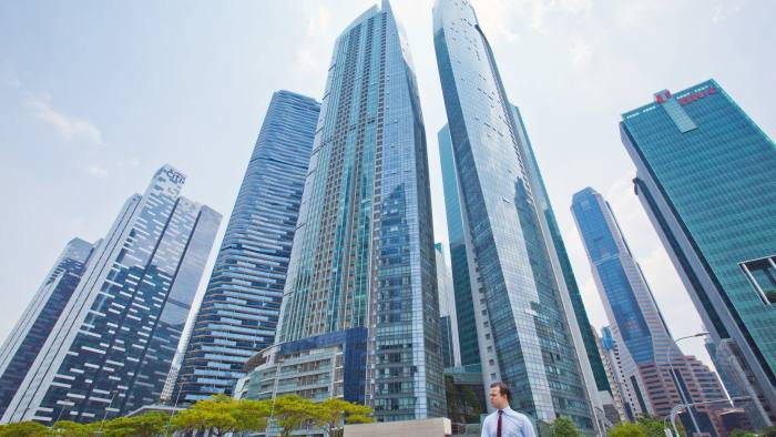 A pedestrian walks in front of commercial buildings in the central business district of Singapore, on Friday, April 8, 2016. Singapore edged past Hong Kong as the worlds No. 3 financial center. The Southeast Asian city-state ranks behind London and New York on the Global Financial Centres Index, according to a survey by London-based research firm Z/Yen Group. Photographer: Sam Kang Li/Bloomberg