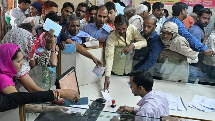 Customers wait to exchange Indian five hundred and one thousand rupee banknotes at a Syndicate Bank branch in Dadri, Uttar Pradesh, India, on Tuesday, Nov. 15, 2016. Over a week since Prime Minister Narendra Modi shocked the nation with the withdrawal of large denomination notes there was no sign the government had managed to print enough notes to replace its withdrawal of 86 per cent of currency in circulation. Photographer: Anindito Mukherjee/Bloomberg