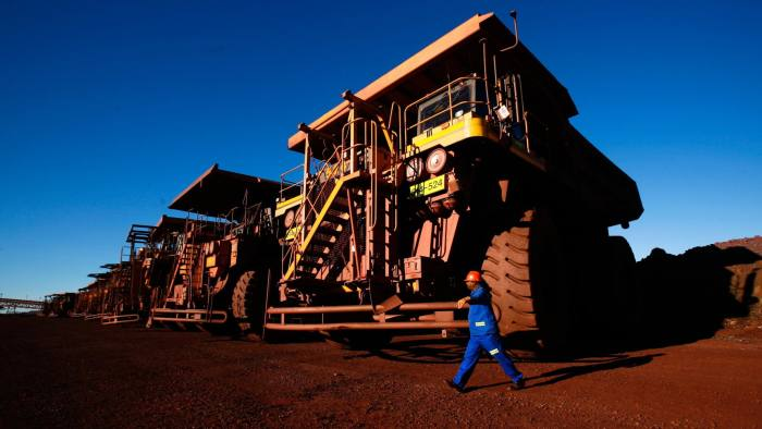 A driver passes a row of Komatsu Ltd. haul trucks at Sishen open cast mine, operated by Kumba Iron Ore Ltd., an iron ore-producing unit of Anglo American Plc, in Shishen, South Africa, on Wednesday, Aug. 24, 2011. Kumba Iron Ore Ltd. may decide on the next stage of its Sishen-Saldanha expansion in 2014, the company said in a presentation on its website today. Photographer: Nadine Hutton/Bloomberg