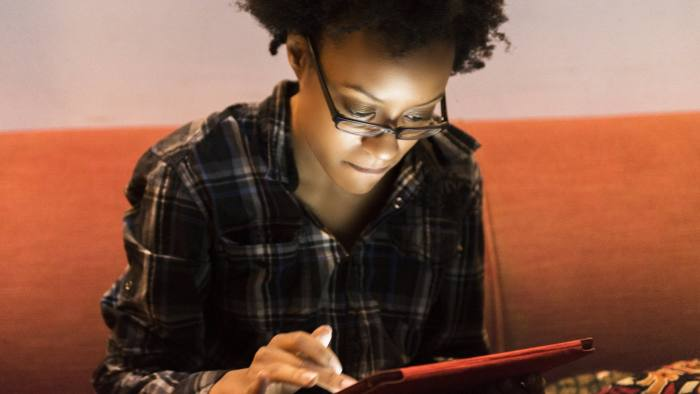 This is a horizontal, close up, color, royalty free stock photograph of an intelligent Black American woman in her 20s browsing the internet with a digital tablet while sitting on the couch in her Brooklyn apartment in New York City. As she scrolls through web pages online the glowing screen illuminates her face. Photographed with a Nikon D800 DSLR camera.