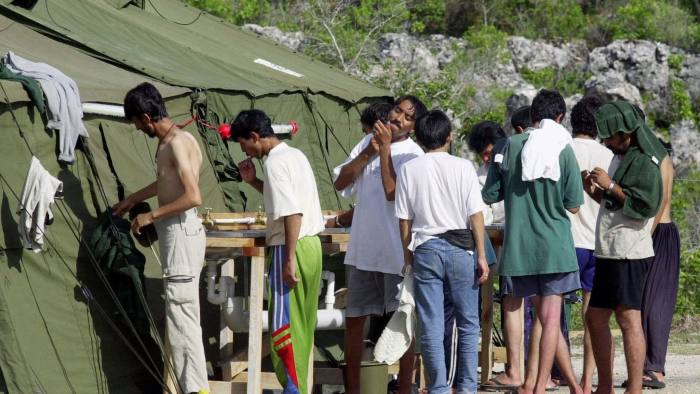 FILE - In this Sept. 21, 2001, file photo, men shave, brush their teeth and prepare for the day at a refugee camp on the Island of Nauru. U.S. officials had stopped screening refugees for potential resettlement in the United States but would return to the Pacific atoll of Nauru to continue working toward a deal that President Donald Trump has condemned as