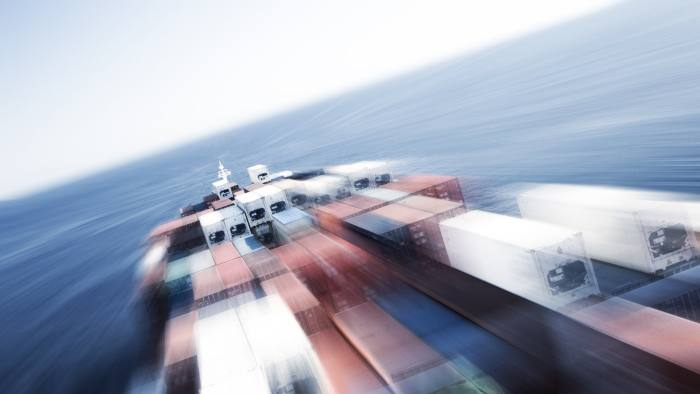 Motion blurred logistic photo of a large container ship making high speed in the ocean