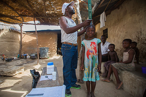 Six-year-old Pinkwat Luka of Amper, Nigeria, is being measured by a community directed distributor (CDD) to ensure that she receives the correct dose of medicine