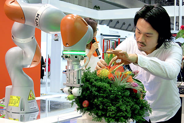 A flower arranger gets an assist by a robot in the booth of German robot manufacturer Kuka during the International Robot Exhibition at the Tokyo Big Sight on December 2, 2015 in Tokyo, Japan