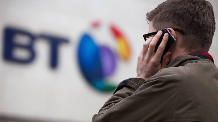 A pedestrian uses a smartphone in this arranged photograph taken outside BT Group Plc's headquarters in London, U.K., on Monday, Dec. 15, 2014. BT started exclusive talks to acquire Deutsche Telekom AG and Orange SA's British wireless venture EE for 12.5 billion pounds ($19.6 billion), moving ahead with a deal that's set to spur more mergers in the U.K. telecommunications market. Photographer: Jason Alden/Bloomberg