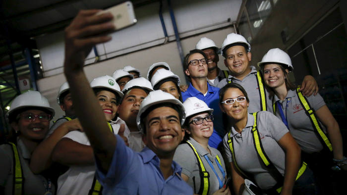 Lorenzo Mendoza, towards the back, in blue shirt, with workers at a Polar distribution centre
