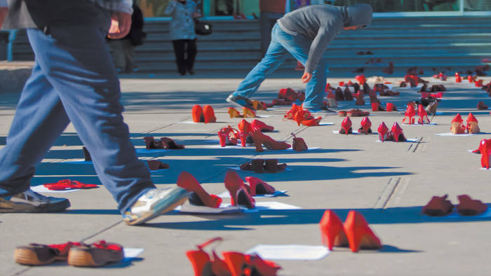 People walk past hundreds of red shoes, symbolizing missing women, left by their relatives in Ciudad Juárez