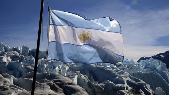 View of an Argentine National flag at the Perito Moreno Glacier in Los Glaciares National Park, Santa Cruz province, Argentina on March 17, 2014. AFP PHOTO / MARIO GOLDMAN