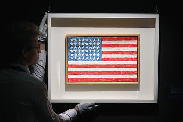 LONDON, ENGLAND - OCTOBER 10: An employee poses with a painting by Jasper Johns entitled 'Flag' during a press preview at Sotheby's on October 10, 2014 in London, England. Due to be auctioned in New York on November 17th, it is expected to fetch in excess of 20 million USD (Photo by Carl Court/Getty Images)