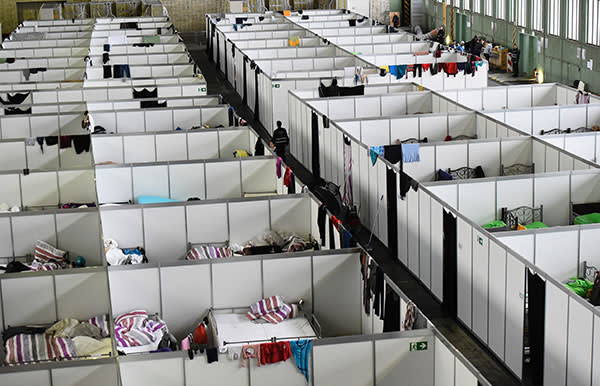 View into rooms in lightweight construction where clothes are hung up at the refugee accomodation at the former Tempelhof airport in Berlin on December 9, 2015.