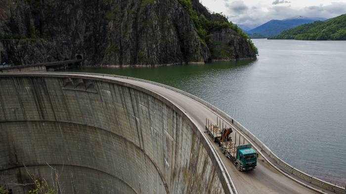 A truck is driven over the dam of Vidraru hydro power plant May 30, 2014. REUTERS/Bogdan Cristel (ROMANIA - Tags: BUSINESS ENERGY TRANSPORT) - GF2EA6212HN01