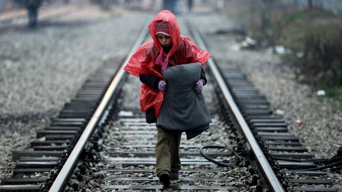 epaselect epa05187796 A boy walks on the railway line wearing a raincoat carrying a blanket at the refugee camp in Idomeni, Greece, as they wait to be allowed to cross the borders with FYROM, 29 February 2016. Macedonian police fired tear gas at hundreds of migrants after they stormed a metal fence along the border with Greece on 29 February, as refugees were blocked from travelling between the two countries on the main route to Western Europe. EPA/SIMELA PANTZARTZI