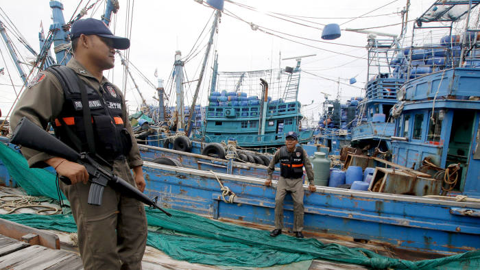 Police officers stand near a fishing boat during an inspection at the pier of Songkhla, south Thailand December 23, 2015
