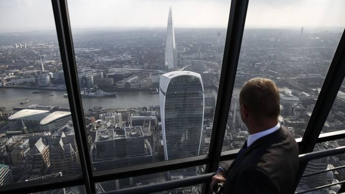 A security guard looks at the view south towards the River Thames and city skyscrapers 20 Fenchurch Street, also known as the Walkie-Talkie, center, and the Shard, center top, from the 51st floor of the Leadenhall Building, also known as the Cheesegrater, in the financial district of London, U.K., on Wednesday, Sept. 3, 2014. Rents for skyscrapers with nicknames like the Walkie Talkie and Cheesegrater rose faster than the rest of the financial district in the last three years, rewarding developers who started construction at a time when the economy was shrinking. Photographer: Simon Dawson/Bloomberg