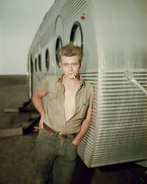 American actor James Dean (1931-1955) leaning against a dressing room trailer with his shirt open to the waist while smoking a cigarette on the set of director George Stevens's film, 'Giant', in which he starred.