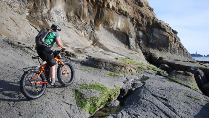 Joe Kidd takes his fatbike over some rocky outcrops on the Oregon coast