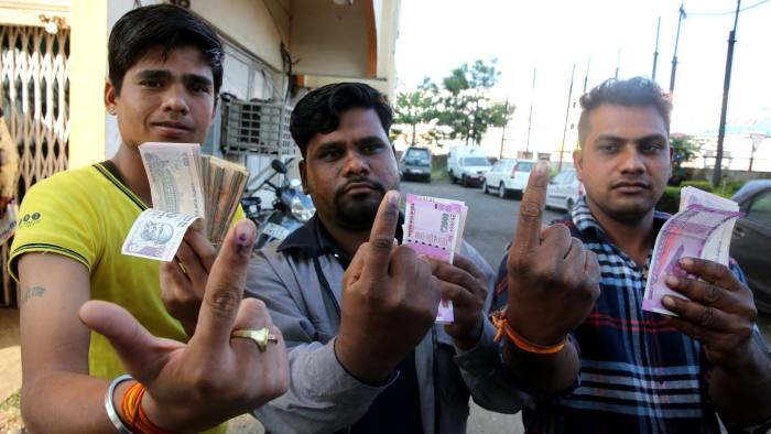 epa05633552 Indian men show their inked fingers as they hold new Indian currency notes at a bank in Bhopal, India, 16 November 2016. Indian Bank officials started leaving an ink mark on fingers of people who have exchanged their discontinued Rupee notes for new ones to prevent people from visiting the branch repeatedly. Indian Prime Minister Narendra Modi announced the elimination of the 500 and 1,000 rupee bills (7.37 and 14.73 US dollars, respectively), hours before the measure took effect at midnight 08 November, for the purpose of fighting against 'black money' (hidden assets) and corruption in the country. The decision sparked some protests, while storekeepers complained about dwindling sales because many citizens lack the cash to buy the most basic products, as lines get longer at ATMs and banks. EPA/SANJEEV GUPTA