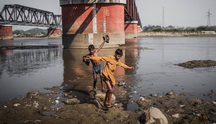 Two boys make their way back to shore after bathing in the heavily polluted Ram Ganga tributary of the Ganges in Moradabad, Uttar Pradesh
